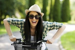 Woman happy on bike not imprisoned by a mini skirt because mini skirts are not good for women