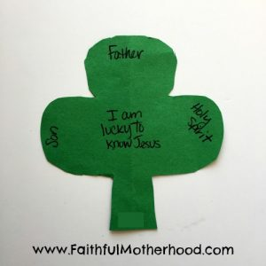 Simple cut out shamrock with words: Father, Son, and Holy Spirit. In the center is written I am lucky to know Jesus. Faith lessons from St. Patrick's Day
