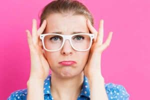 Woman stress and wants to simply your family life, blue shirt with glasses and a hot pink background.
