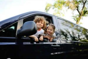 2 kids poking their heads out of a black minivan which is filled with car hacks for moms