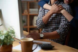 Woman hugging her husband from behind when he is sitting at workplace