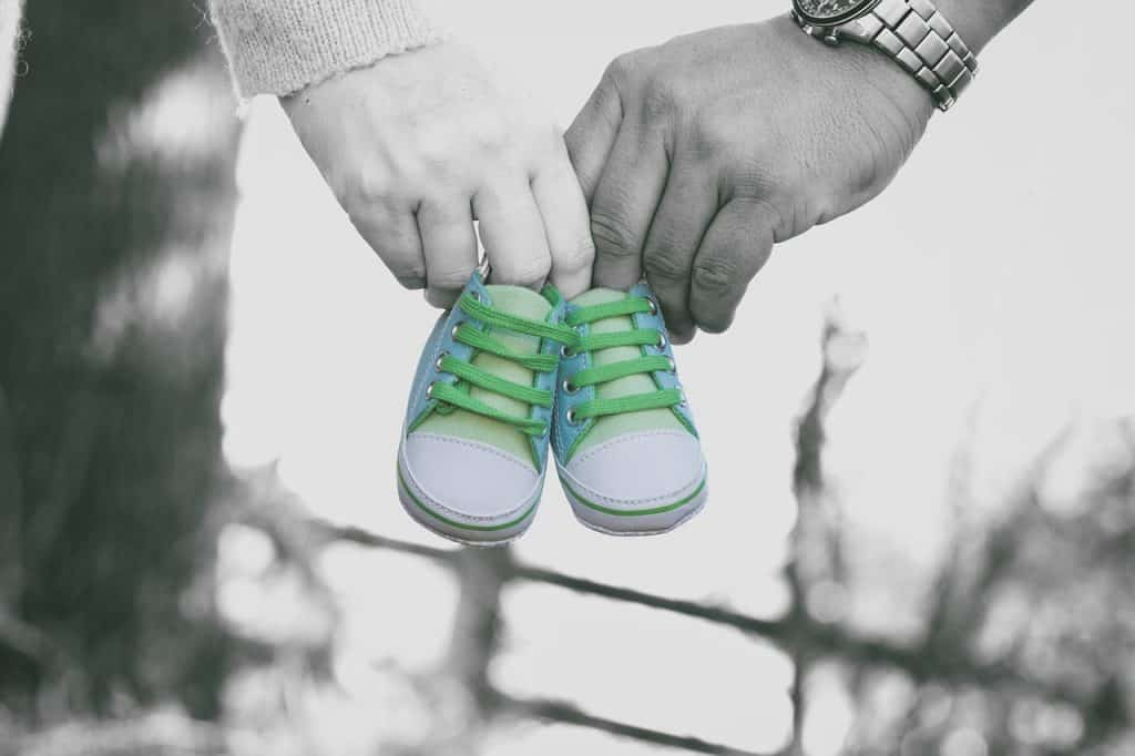 Overcome Miscarriage Fears - Parents holding little baby shoes