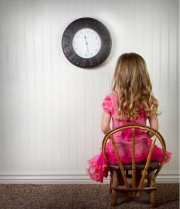 A young child in time out or in trouble, with clock on wall