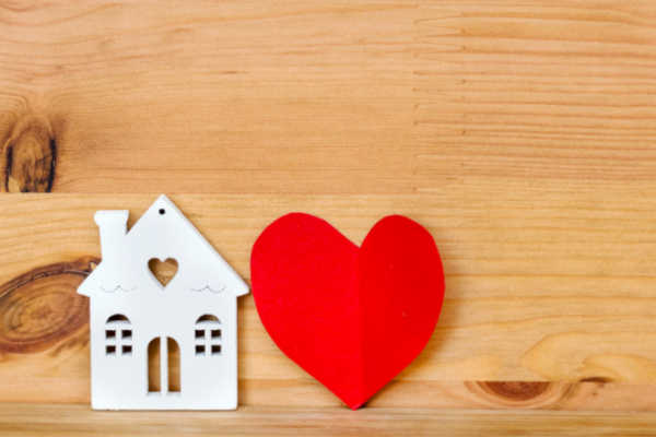 What is a homemaker? Small cutout house with red heart on wooden background