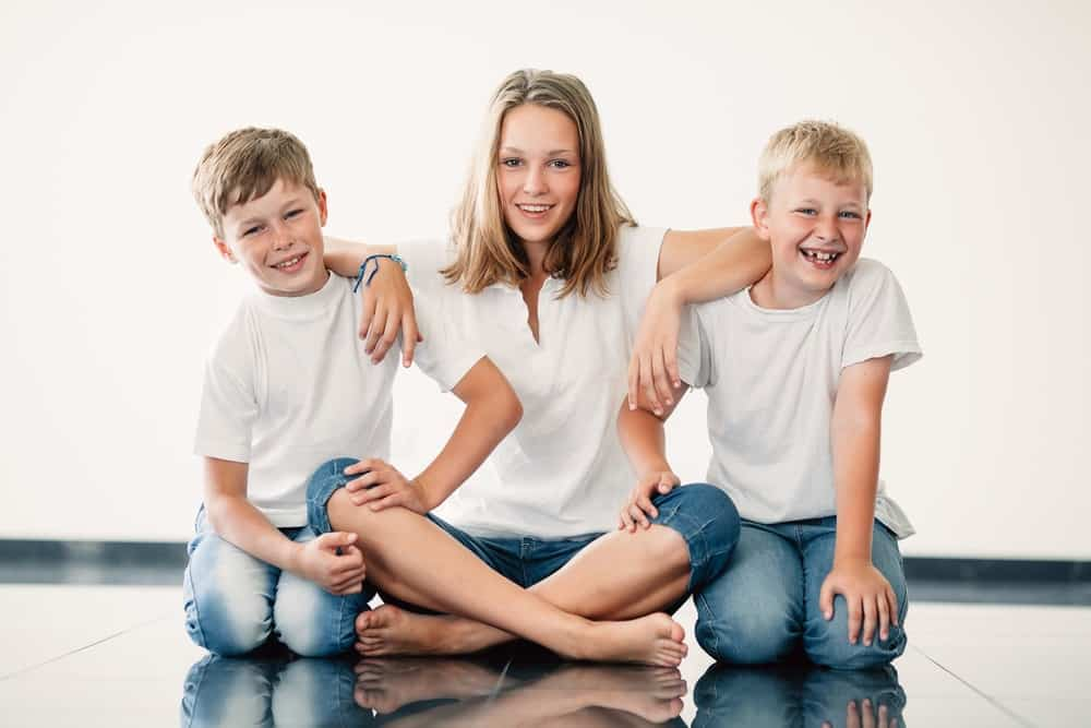 A sister with two younger brothers laughing. Title: Surprising ways that having siblings grows stronger faith