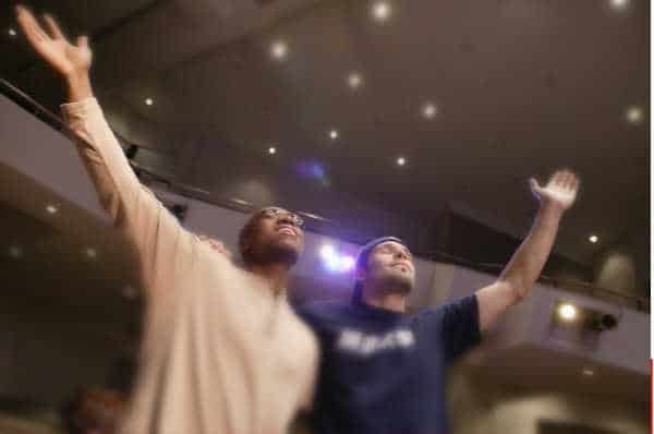 Two men with hands raised in worship - find a church your husband likes