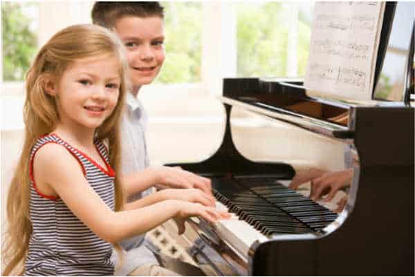 girl and boy playing hymns on a piano