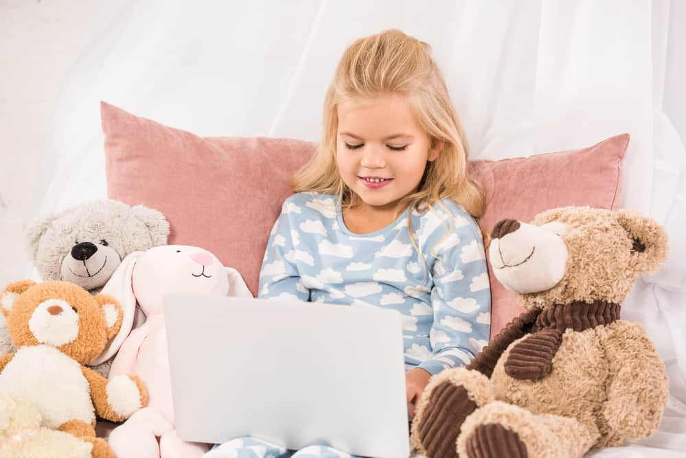 Little girl watching a laptop screen surrounded by teddy bears while her mother has quiet time with God.