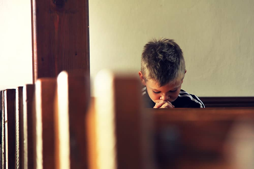 Young boy with his head bowed in prayer in a church pew. A penitent child saved and ready for baptism.
