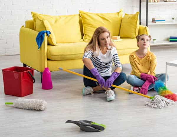 Mom and daughter frustrated and tired from cleaning all the clutter at their house.  A good reason to teach kids to declutter and have less housework.