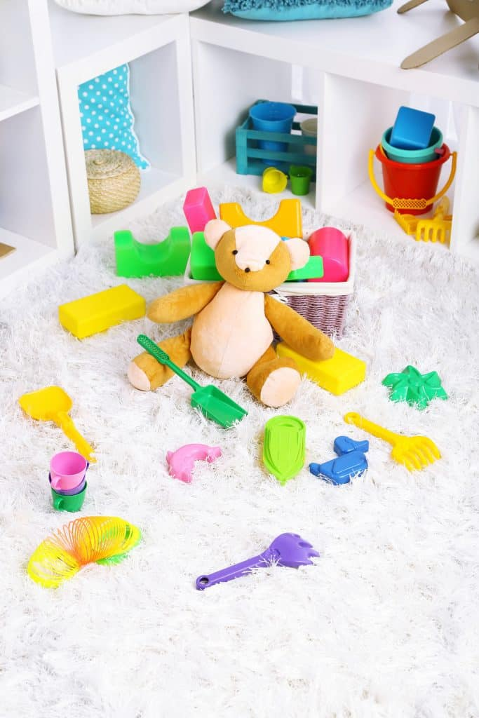 Colorful kids toys all over the floor and bookcase. - Teach kids to declutter biblically so they give away extra toys.