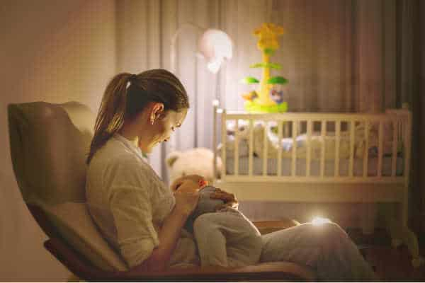 Sleep deprived mom nursing her newborn in the dark of night. Tired mom care giving while others are asleep.