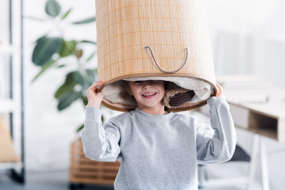Happy little young man holding a laundry basket over his head - he is helping out because it is a smart mom laundry hack and tip.