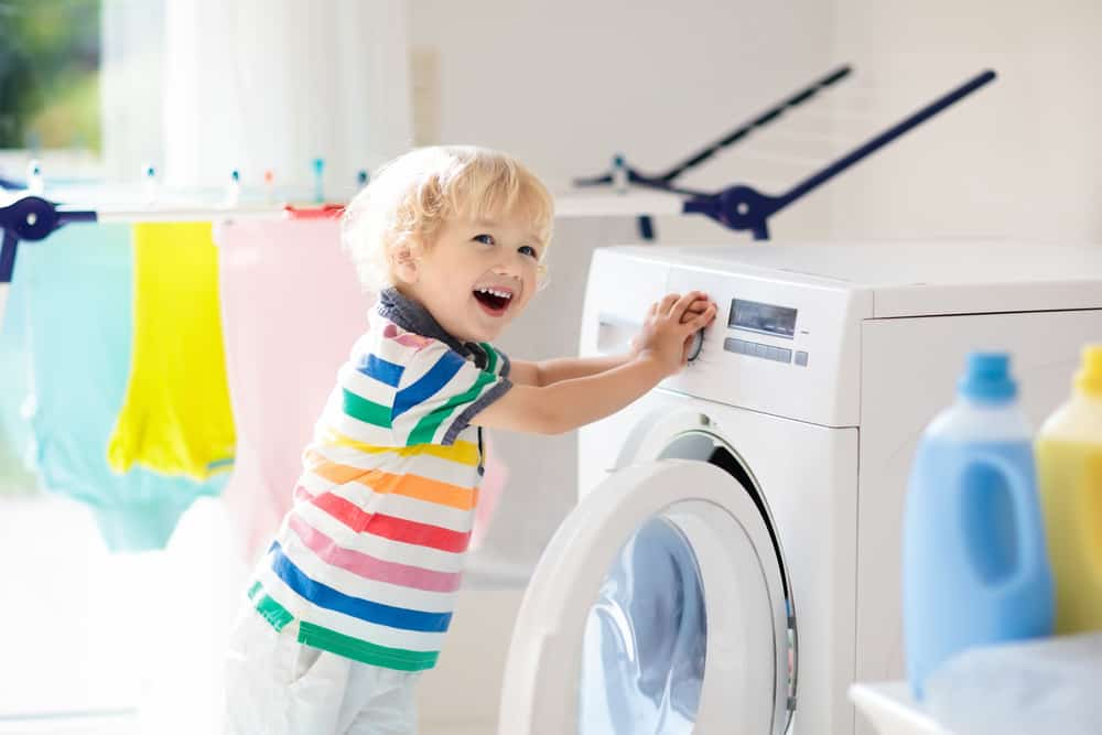 Little boy in rainbow striped shirt is helping with laundry in a bring laundry room.