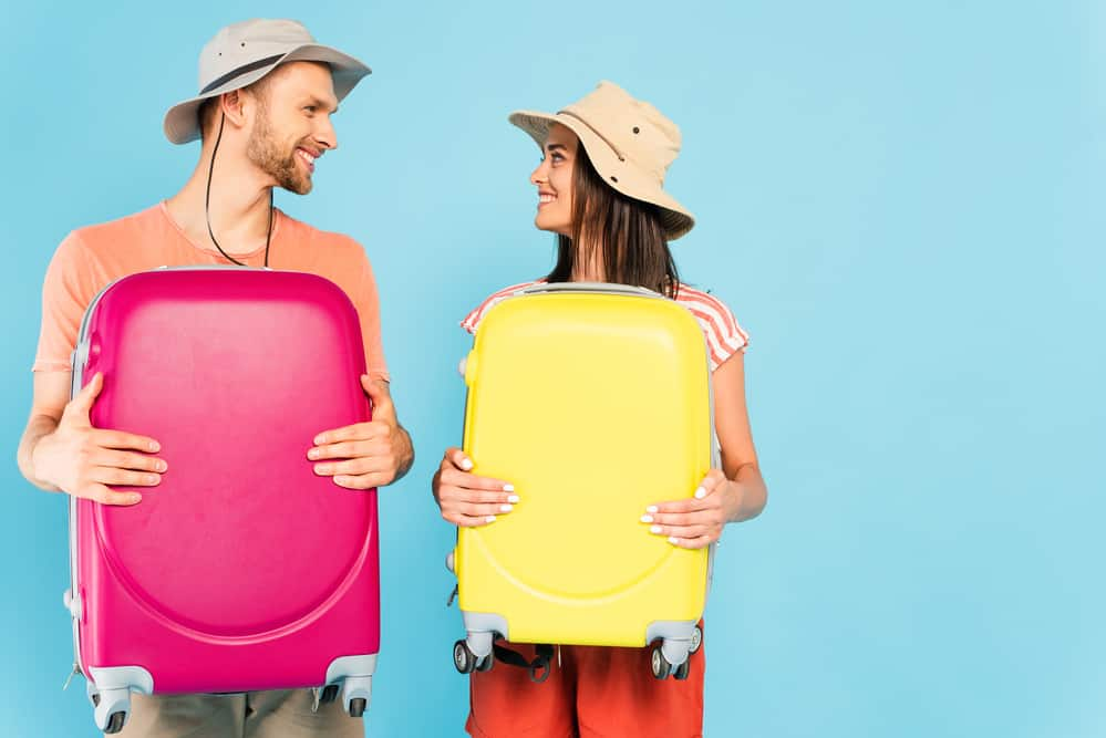 Couple holding colorful luggage and smiling at each other.