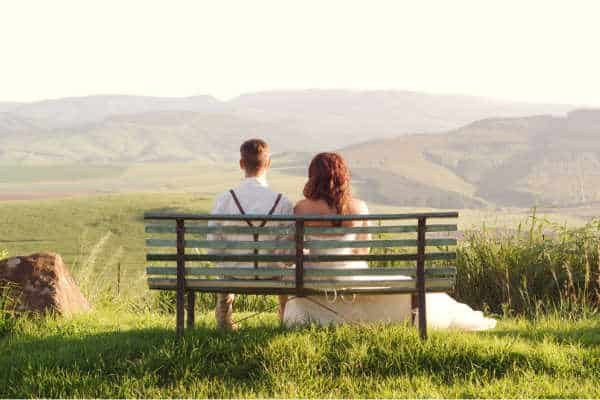 Young married couple sitting on a bench starring out at a beautiful mountain scene not knowing that they need preventative Christian marriage counseling.