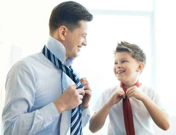 Dad and son putting on ties while they are getting dressed for church