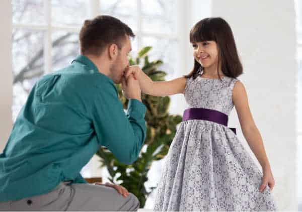 Young girl is getting dressed for church and her dad is holding her hand and kneeing in front of her in approval.