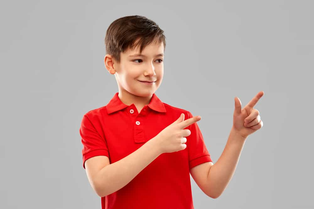 Happy, young boy pointing his fingers.  This kid dressed for church in a red polo shirt.