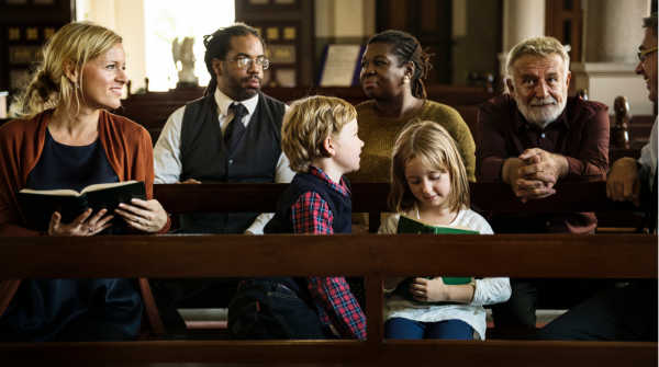 Kids dressed for church and sitting with their parents in the pew.  Other adults behind them are getting ready for church.