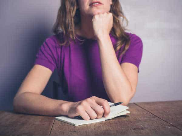 Tired homeschool mom isn't going to quit homeschooling, instead she is writing down her blessings in a journal.  She is wearing a purple blouse and the table is dark wood.