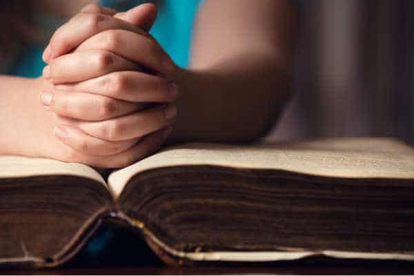 Woman in a turquoise blue shirt with her hands clasped in prayer over a very old Bible - example of pray without ceasing