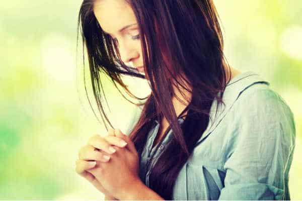 Closeup portrait of a young caucasian woman praying, against abstract green background - how to pray without ceasing