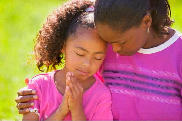 Black mother praying with her black daughter.  Both in purple and pink shirts. Serene and peaceful picture - pray without ceasing