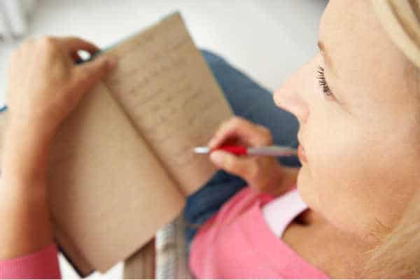 Woman in pink shirt is writing in a brown journal. Writing is one way of praying without ceasing.