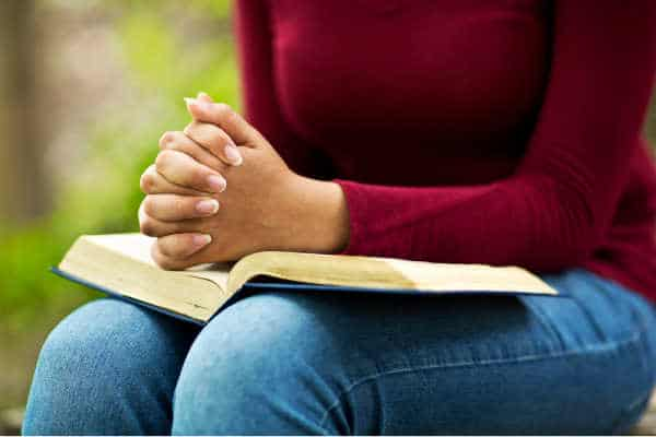 Woman in red/maroon top and jeans seated with a Bible open on her lap and her hands folded in prayer.