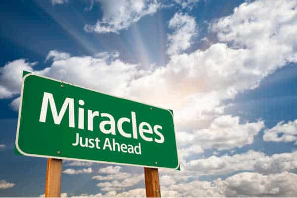Green road sign that says Miracles - Just Ahead