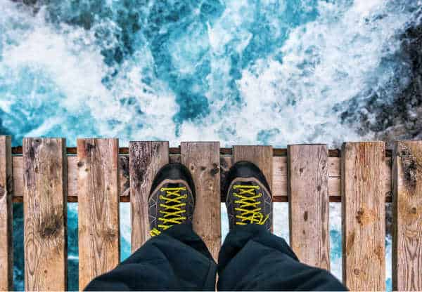 Person with hiking boots standing on the endge of a rough wooden bridge over roaring water - person waiting for God to part the water.