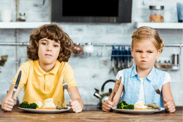 Two kids with forks and knives raised and full plates of yummy food with mad and frustrated faces - just like when God's kids complained about their food too