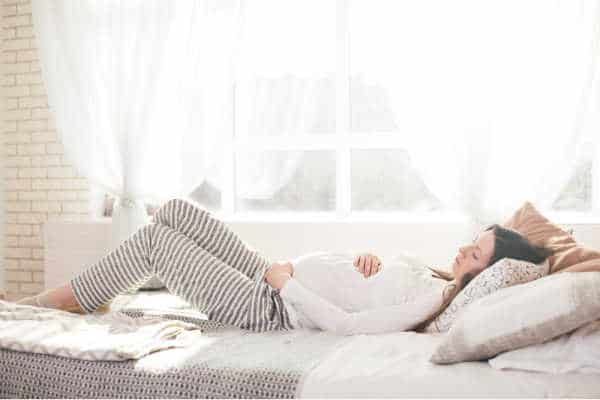 Pregnancy woman lying in bed.  She is wearing a white top and grey and white striped lounge pants.  She has her hands wrapped around her belly. Her eyes are downcast and she is meditating on pregnancy Bible verses.