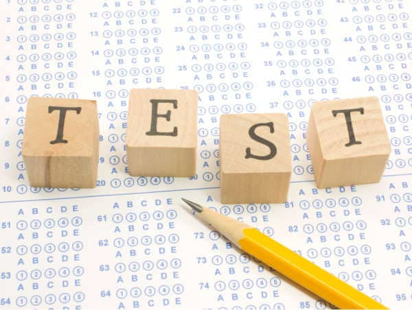 A standardized test with a sharpened number 2 pencil and blocks that spell out test - the importance of Sunday school should be shown in testing