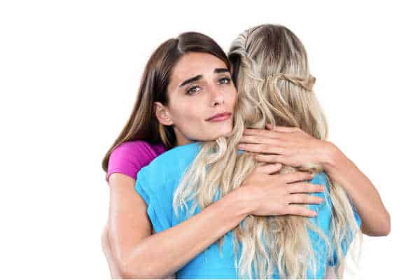 Sad young woman hugging friend on white background - comforting her despite miscarriage fears, pregnancy fears