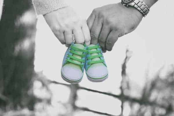 man and woman in black and white holding a pair of blue and turquoise baby shoes just like a pregnancy announcement - which miscarriage fears can cause couples to wait to announce