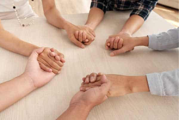 Group of women holding hands on a table - supporting each other through miscarriage fears, pregnancy fears