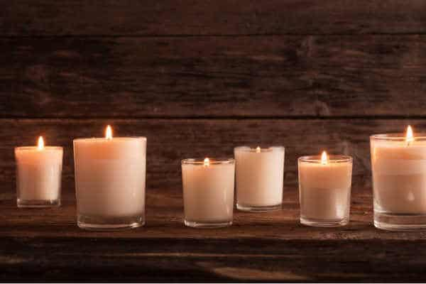 six white candles glowing on a wooden background set up like a memorial to lost children for women with miscarriage fears