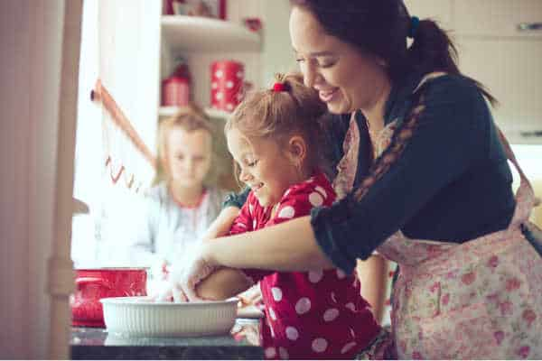 Mom and children baking at Christmas time, it counts as homeschooling during the holidays.