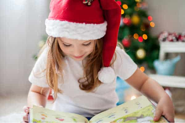 Little girl with Santa hat reading a book, because she is homeschooling during the holidays, with a Christmas tree in the background.