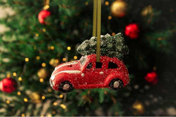 Little toy car ornament with Christmas tree to symbolizing traveling while homeschooling during the holidays.