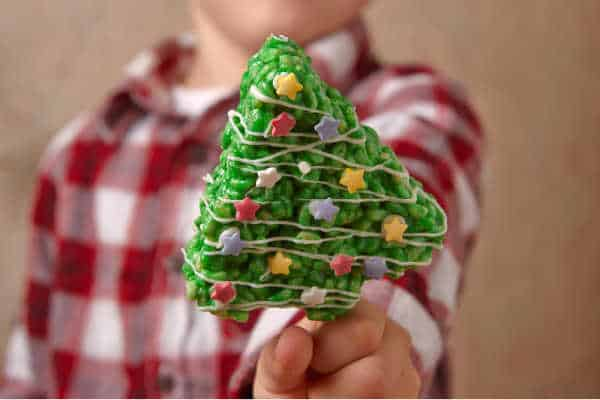 Homeschooling during the holidays can be challenging if your little guy in a plaid shirt is holding up a rice Krispie treat Christmas tree.