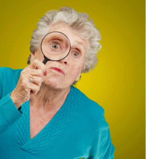 Elderly woman with white hair and a blue shirt holding up a magnifying glass as she prepares to interrogate your child about homeschooling.