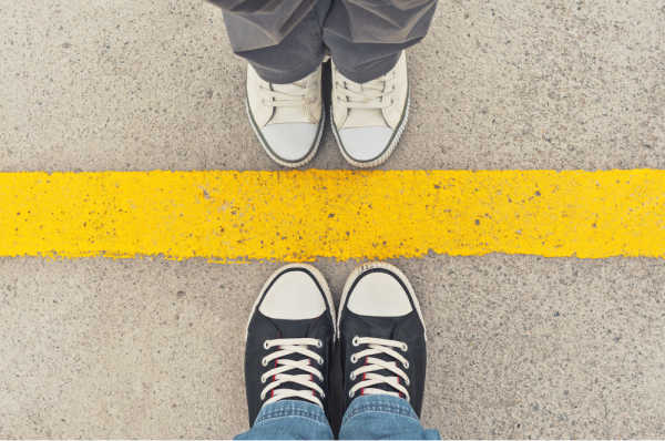 Two seats of sneaker-ed feet standing opposite a yellow line - set boundaries with family regarding homeschool