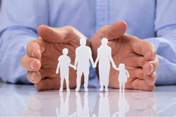 Father and Husband's hands surrounding his family - a paper cut out of parents with kids. Symbolizes what it looks like to set boundaries with family regarding homeschooling and protecting your family from anti-homeschooling relatives.