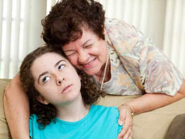 Teen puts up with a hug from an annoying aunt or parent - she needs to set boundaries with family