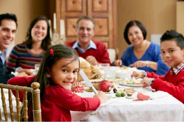 Set boundaries with your family regarding homeschooling and be able to enjoy a peaceful joy family dinner like the one pictured here.  Family is seated around a giant turkey, dressed in bright primary colors.