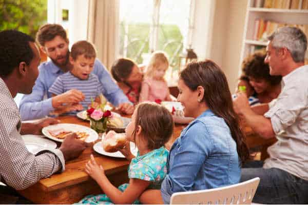 Set boundaries with family regarding homeschool and be able to enjoy a happy family gathering like the one pictures.  A diverse family with adults and children laughing and eating.