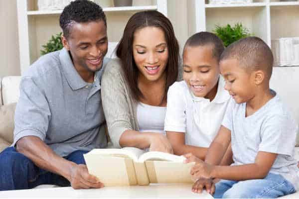 A happy African American man, woman and boys, father, mother and two sons, family sitting together at home studying the bible together because they dislike the children's ministry at church.